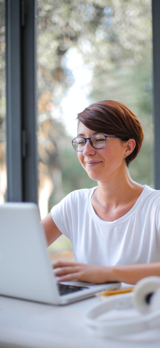 Frau mit Brille und kurzen Haaren am Laptop